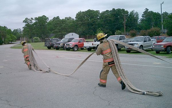 Two firefighters carrying hose