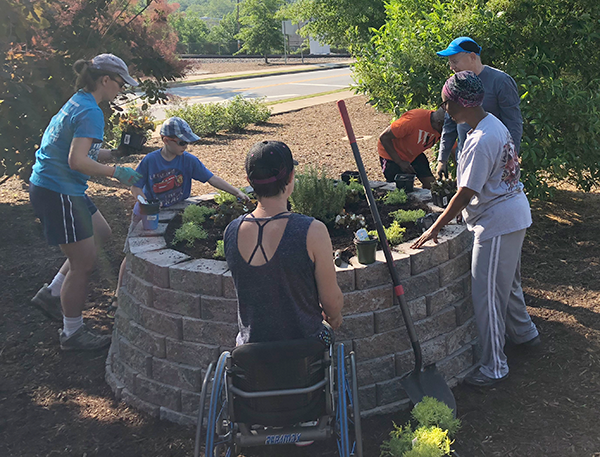 Neighbors working together to add plantings to a community planter in the Green Avenue neighborhood