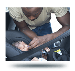 Man buckling infant into a car seat