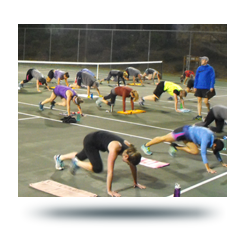 Bootcamp participants doing push-ups on tennis court